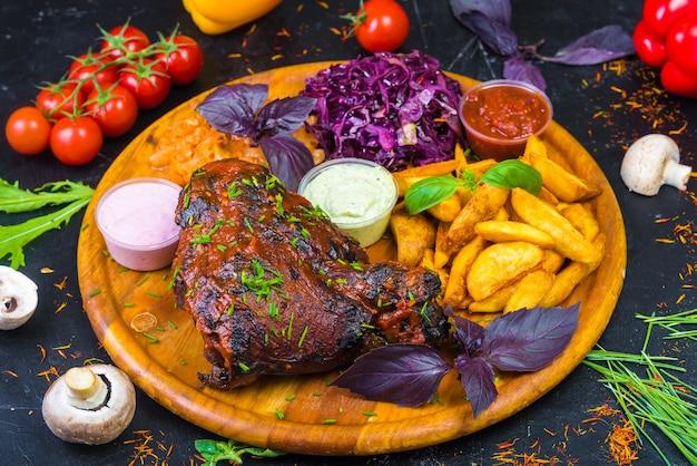 Golonka rumiana, pieczona na desce z warzywami, sosem i świeżymi ziołami.
