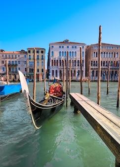 Gondola zacumowana przy molo na canal grande w wenecji, włochy.