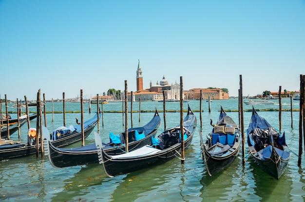 Gondole zacumowane przez plac świętego marka z kościołem san giorgio di maggiore w wenecji, włochy