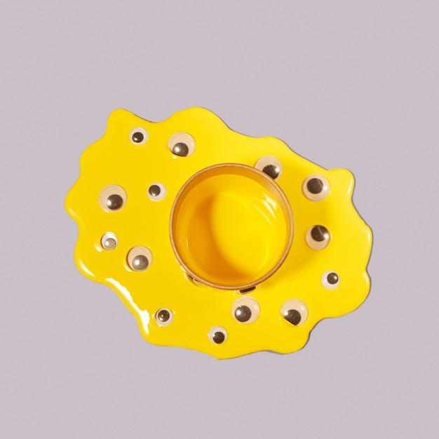 Googly plastikowe oczy w kałuży rozlanej żółtej farby wokół puszki na szarym tle z cieniami, kopia przestrzeń. widok z góry.