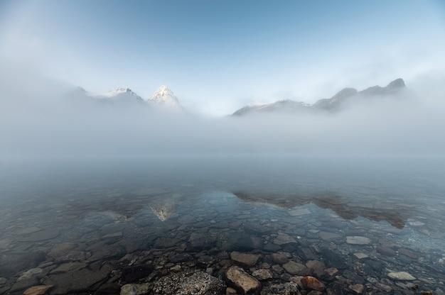 Góra assiniboine w niebieskim, mglistym odbiciu nad jeziorem magog rano w parku prowincjonalnym, bc, kanada