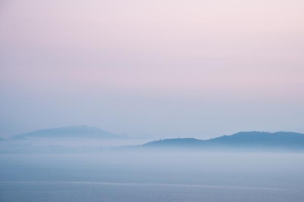 Góra i morze pokryte rannej mgle przed wschodem słońca.