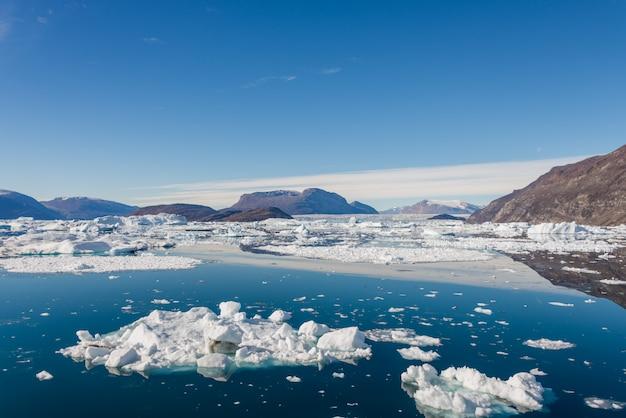 Góra lodowa w fiordu grenlandii z odbiciem w spokojnej wodzie. słoneczna pogoda. złota godzina.
