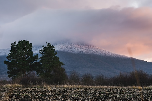 Góra pokryta śniegiem i zachmurzone niebo podczas zachodu słońca