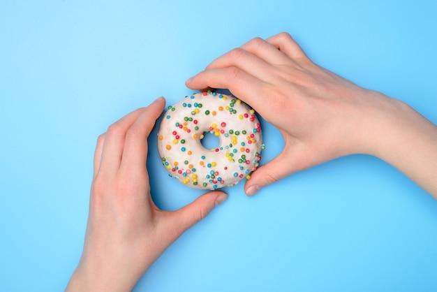 Góra powyżej płasko leżącego płasko nad głową widok z bliska zdjęcie rąk biorących udział w zakupie smacznego świeżego słodkiego pączka gotowego do spożycia na białym tle na tle stołu w pastelowych kolorach
