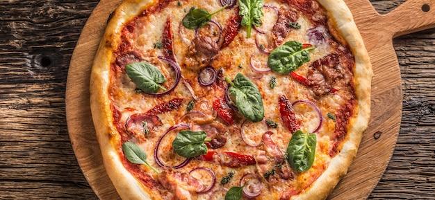 Góra wiew włoskiej pizzy na drewnianym talerzu i okrągłej desce.