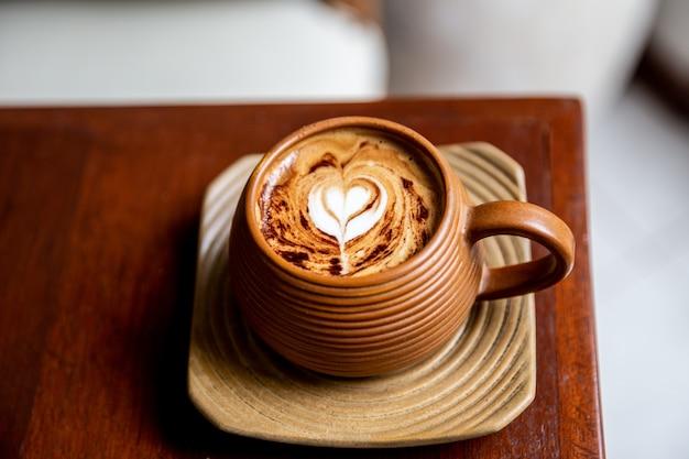 Gorąca brązowa filiżanka cappuccino na drewnianym stole w tle jedna filiżanka do porannej rutyny widok z góry