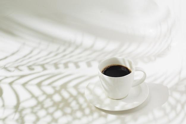 Gorąca czarna kawa i sylwetka liści palmowych