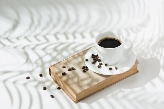 Gorąca czarna kawa z ziaren kawy na nowoczesnym tle