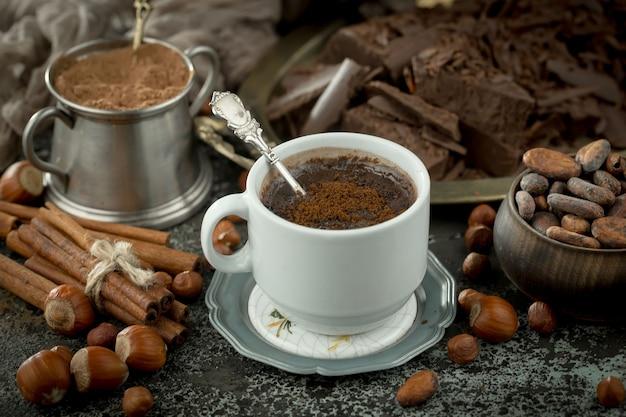 Gorąca czekolada na starym tle w składzie z ziaren kakaowych i orzechów.