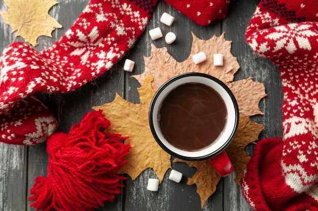 Gorąca czekolada w czerwonym kubku. ozdobiony żółtymi liśćmi klonu, piankami.