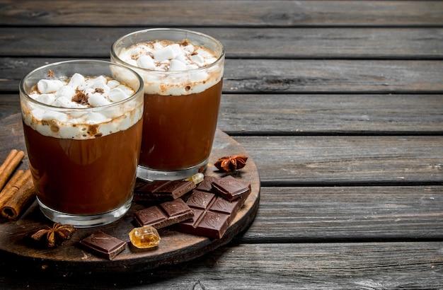 Gorąca czekolada w kubkach z piankami i pachnącym cynamonem na rustykalnym stole.