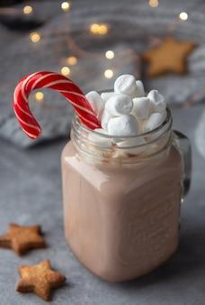 Gorąca czekolada w szklanym kubku z piankami i trzciny cukrowej na szarym tle z girlandami i dzianinowym szalikiem