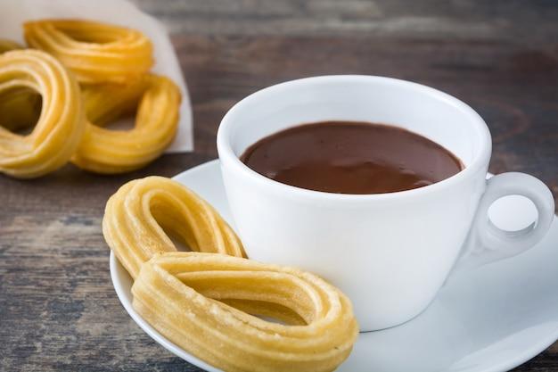 Gorąca czekolada z churros na drewnianym stole hiszpańskie śniadanie