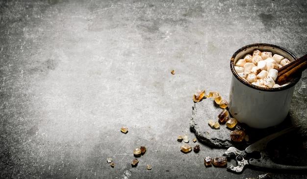 Gorąca czekolada z cynamonem i ciemnym cukrem. na kamiennym tle.