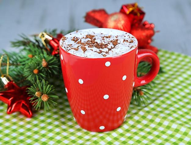 Gorąca czekolada z kremem w kolorowym kubku, na serwetce, na tle ozdób choinkowych