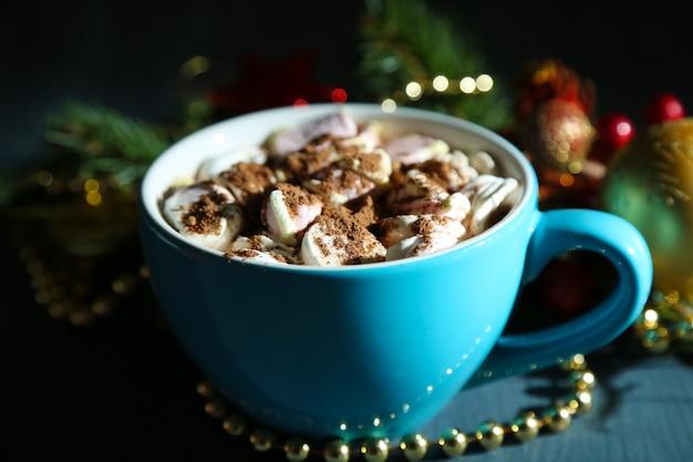 Gorąca czekolada z kremem w kolorowym kubku, na stole, na tle ozdób choinkowych