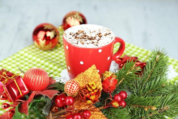 Gorąca czekolada z kremowym kubkiem, na serwetce, na powierzchni ozdób choinkowych