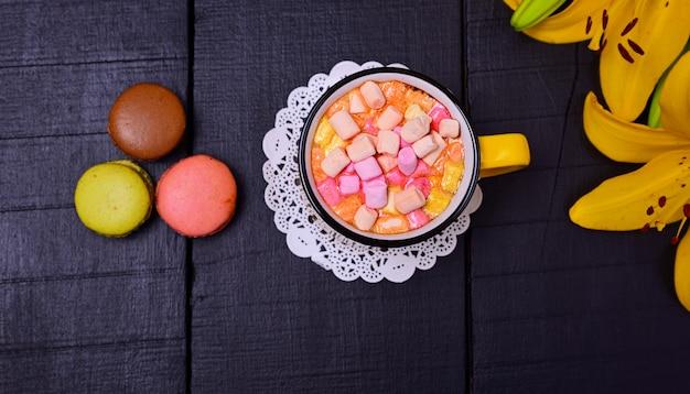 Gorąca czekolada z marshmallows na czarnym drewnianym tle, odgórny widok