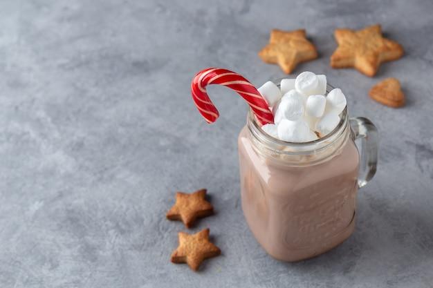 Gorąca czekolada z mlekiem, piankami i trzciną cukrową w szklanym kubku z imbirowymi ciasteczkami na szarym tle.