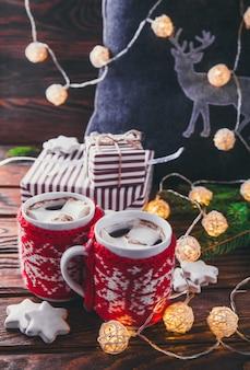 Gorąca czekolada z pianką i herbatnikiem na ozdobach świątecznych girlanda z jelenia jodła