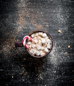 Gorąca czekolada z pianką i karmelem. na czarnej tablicy.