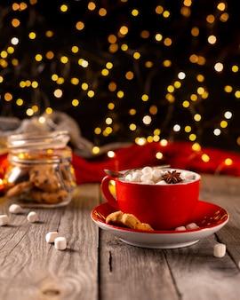Gorąca czekolada z pianką marshmallow w czerwonej filiżance na drewnianym stole