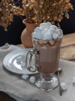 Gorąca czekolada z pianką marshmallow w szklanym kubku na drewnianym stole gorący napój i gałązka świerkowa