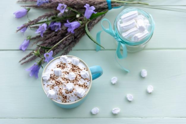 Gorąca czekolada z pianką z bitego mleka i piankami w niebieskim kubku. na turkusowym tle.