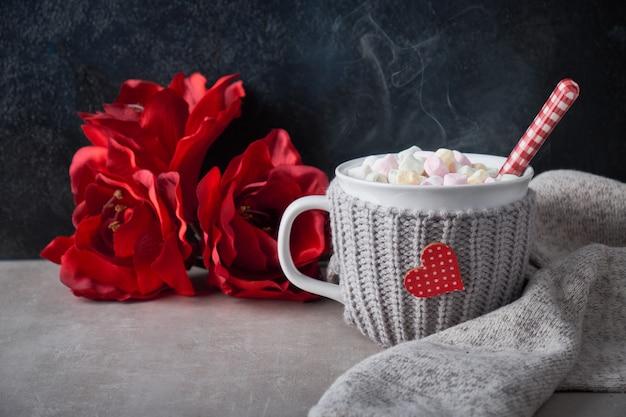 Gorąca czekolada z piankami, czerwone serce na filiżance na stole z zimowymi dekoracjami