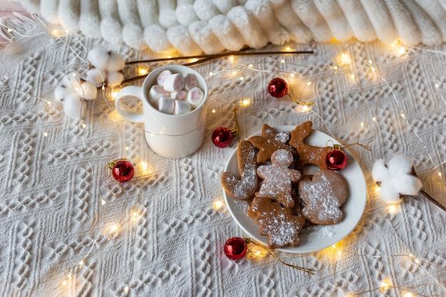 Gorąca czekolada z piankami i ciasteczkami imbirowymi, świąteczna lekka girlanda i czerwone zabawki choinkowe na białym łóżku