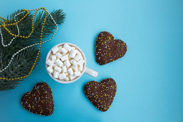 Gorąca czekolada z piankami w białej filiżance i świąteczną kompozycją na niebiesko