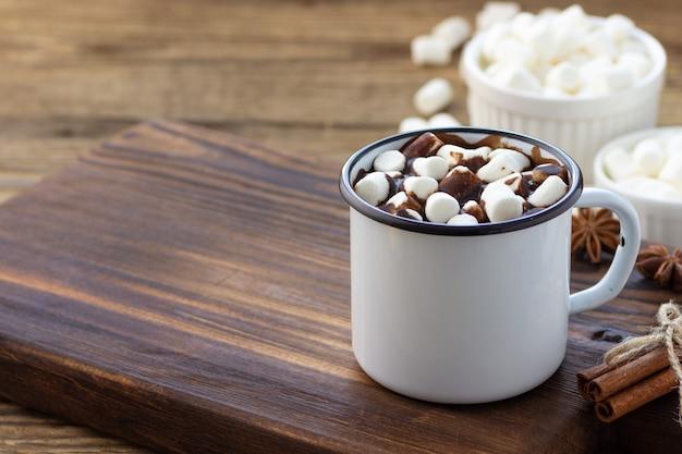 Gorąca czekolada z piankami w białym metalowym kubku vintage