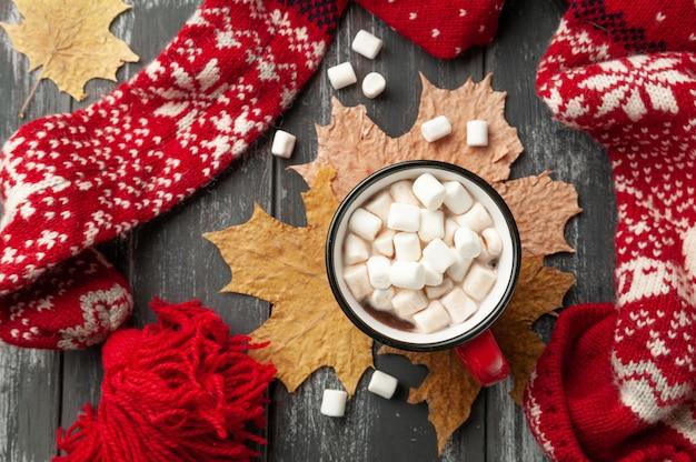 Gorąca czekolada z piankami w czerwonym kubku. ozdobiony żółtymi liśćmi klonu, piankami
