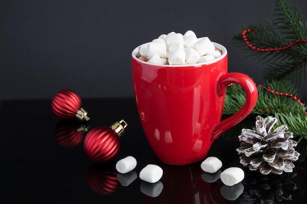 Gorąca czekolada z piankami w czerwonym pucharze i świąteczna kompozycja na czarnym tle. zbliżenie.