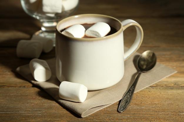 Gorąca czekolada z piankami w kubku, na drewnianym tle
