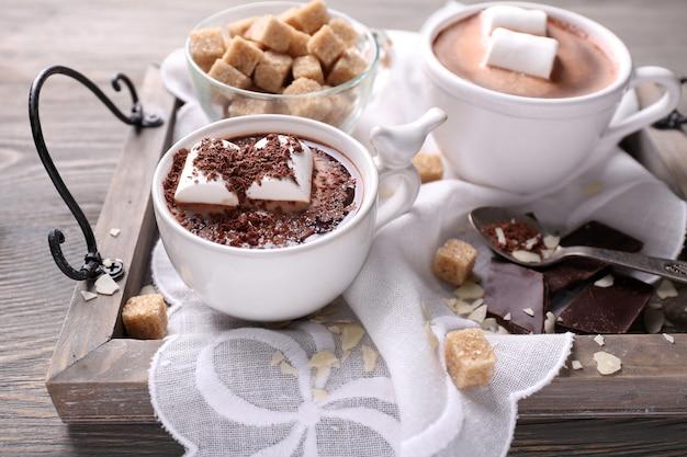 Gorąca czekolada z piankami w kubku, na tacy, na kolorowej drewnianej powierzchni