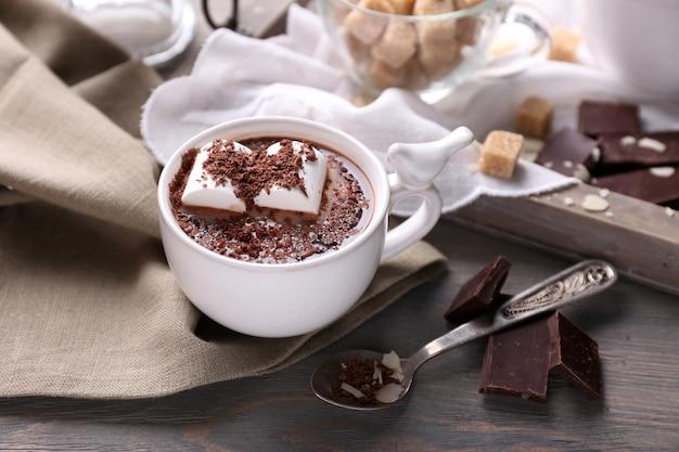 Gorąca czekolada z piankami w kubku, na tacy, na kolorowym drewnianym tle