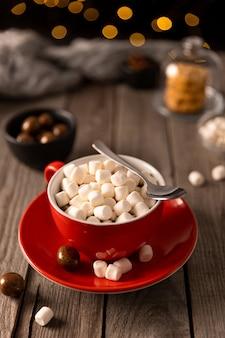 Gorąca czekolada z ptasie mleczko w czerwonej filiżance na drewnianym stole. świąteczny przepis na zimowy gorący napój