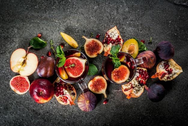 Gorąca czerwona sangria owocowa z jabłkami, śliwkami, figami, granatem i przyprawami