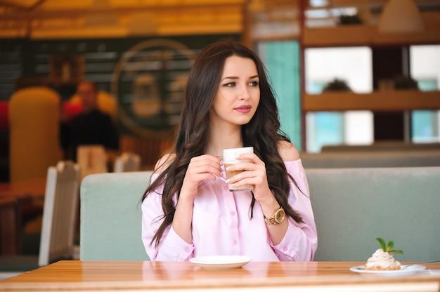 Gorąca filiżanka kawy lub cappuccino w rękach.