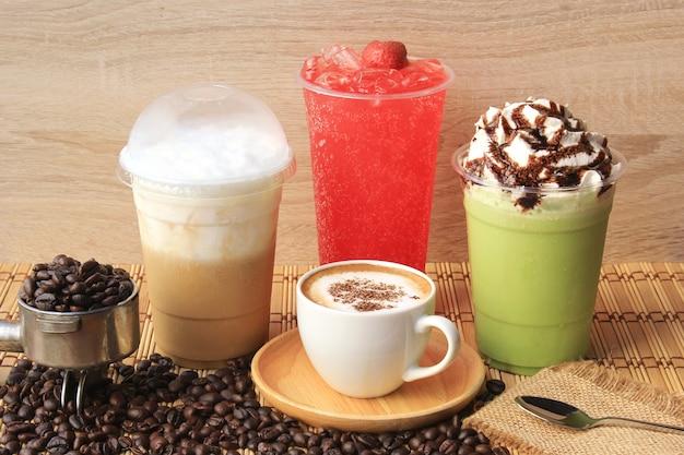 Gorąca filiżanka kawy z ziaren kawy na drewnianym stole, zimna kawa, mrożona matcha zielona herbata i soda owocowa na letni napój