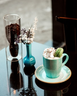 Gorąca filiżanka kawy ze śmietaną i makaronikiem