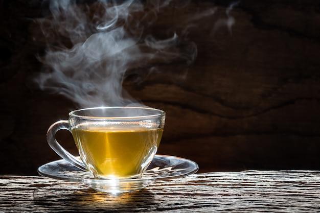 Gorąca herbaciana filiżanka na drewnianym tle