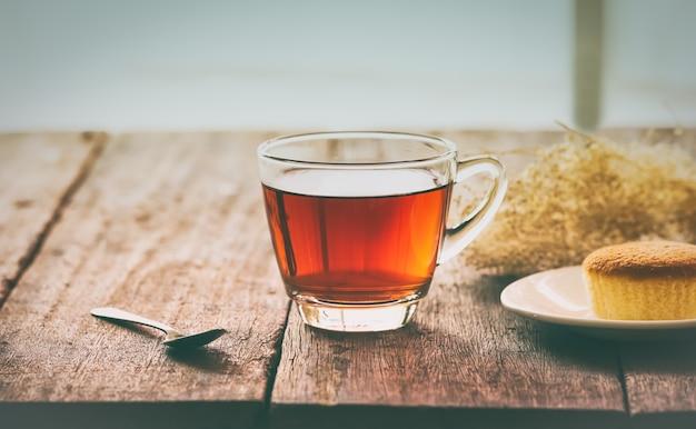 Gorąca herbaciana filiżanka z masło tortem na stole na zima dniu, rocznika tonowanie