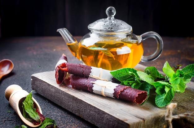 Gorąca herbata miętowa w dzbanku do herbaty i rolka ze skórki suszonych owoców