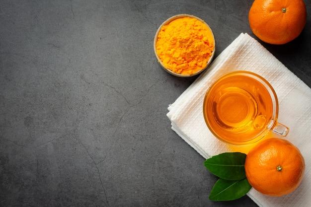 Gorąca herbata pomarańczowa i świeża pomarańcza na stole