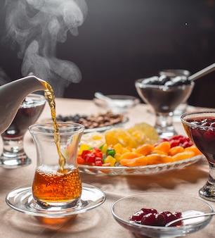 Gorąca herbata wlewa się do szklanki armudu w tradycyjnym azerbejdżańskim zestawie do herbaty
