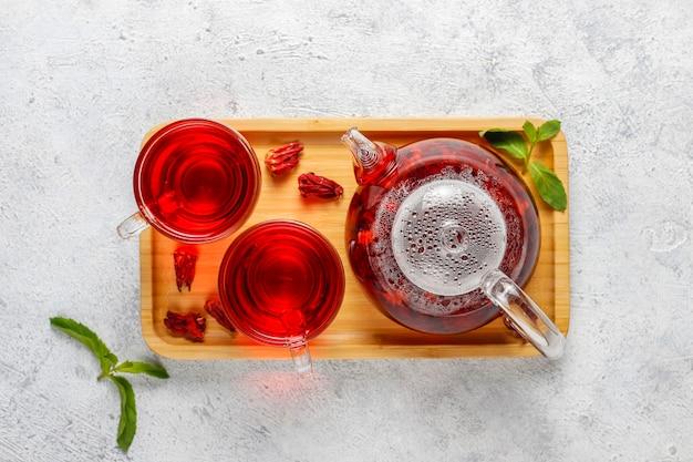 Gorąca herbata z hibiskusa w szklanym kubku i szklanym imbryku.
