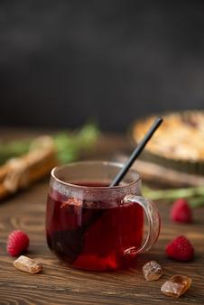 Gorąca herbata z hibiskusa z cynamonem i cukrem na drewnianym stole